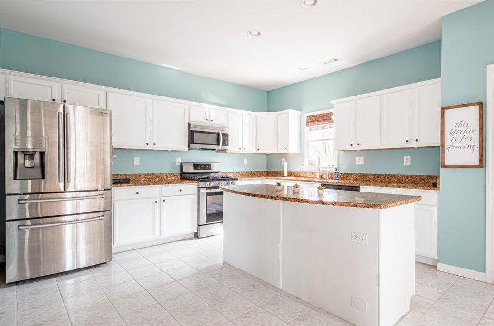 A white and blue kitchen with a stainless steel fridge at left.