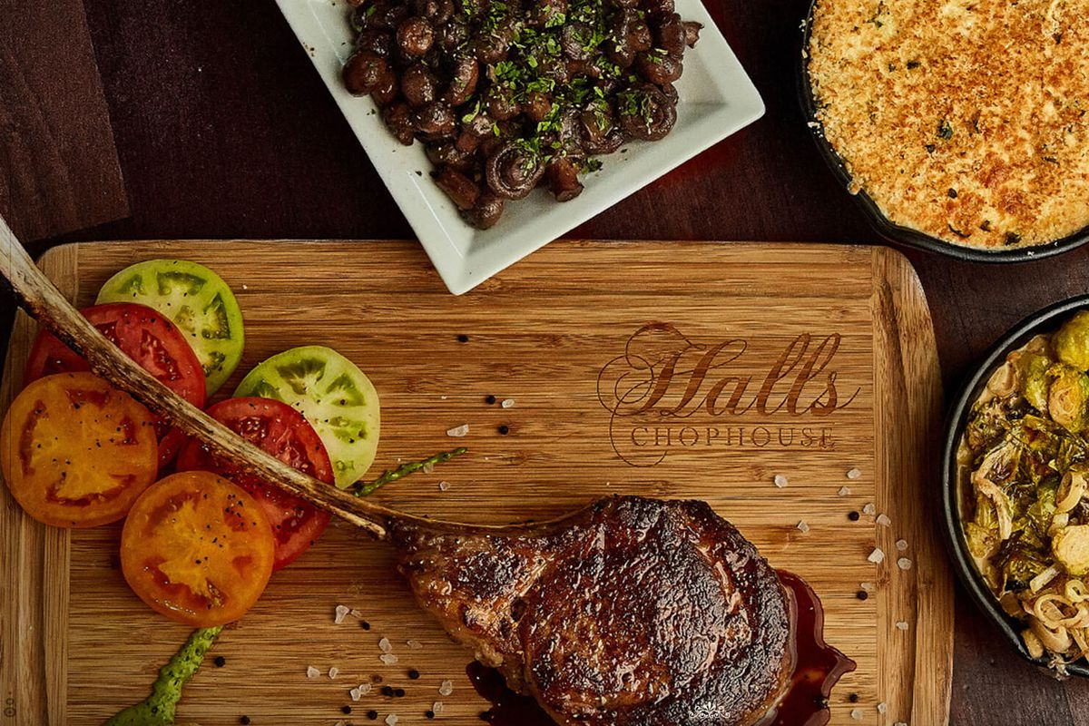 a cutting board labeled Halls Chophouse holds a large cut of meat, surrounded on the right by assorted side dishes