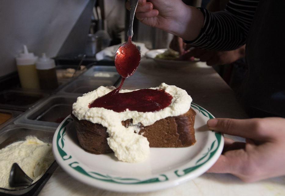 Jam bring spread onto ricotta toast at Sqirl.