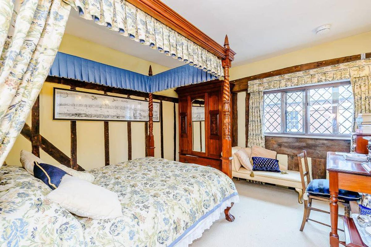 .Bedroom with four-poster bed, wooden cabinet and desk, and a cream daybed by the window.