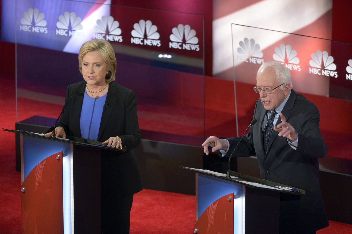 Hillary Clinton and Bernie Sanders, behind podiums, at a presidential debate