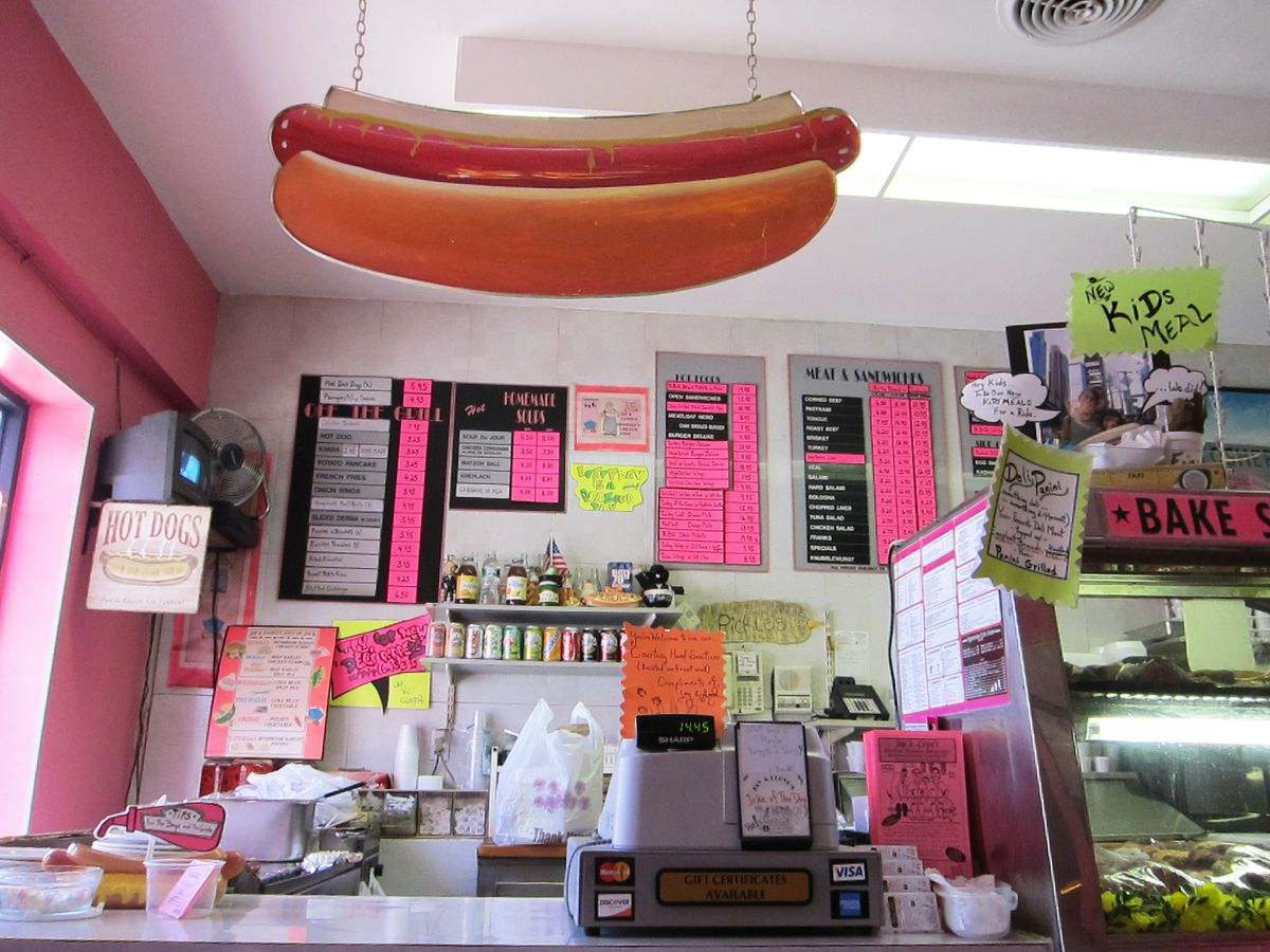 A hot dog hangs over the cash register.