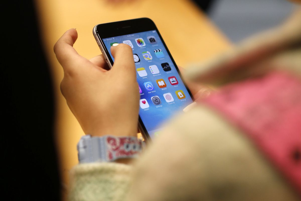 FILE - In this Sept. 25, 2015, file photo, a child holds an Apple iPhone 6S at an Apple store on Chicago's Magnificent Mile in Chicago. The World Health Organization Wednesday, April 24, 2019, issued its first-ever guidance for how much screen time childr