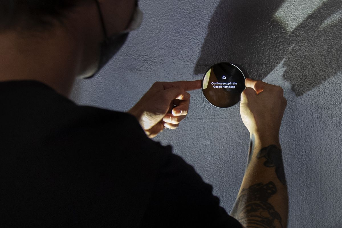 A person operating a Google Nest smart thermostat.