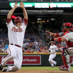 Philadelphia Phillies' Carlos Ruiz, right, reaches over to tag out Arizona Diamondbacks' Lyle Overbay during the first inning of a baseball game Monday, April 23, 2012, in Phoenix.