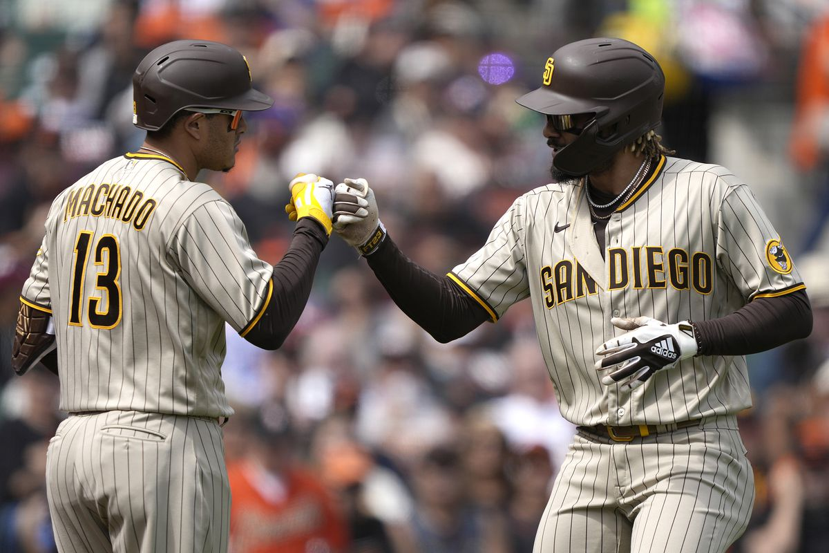 Fernando Tatis Jr. of the San Diego Padres is congratulated by Manny Machado after Tatis hit a solo home run against the San Francisco Giants in the top of the third inning at Oracle Park on September 16, 2021 in San Francisco, California.