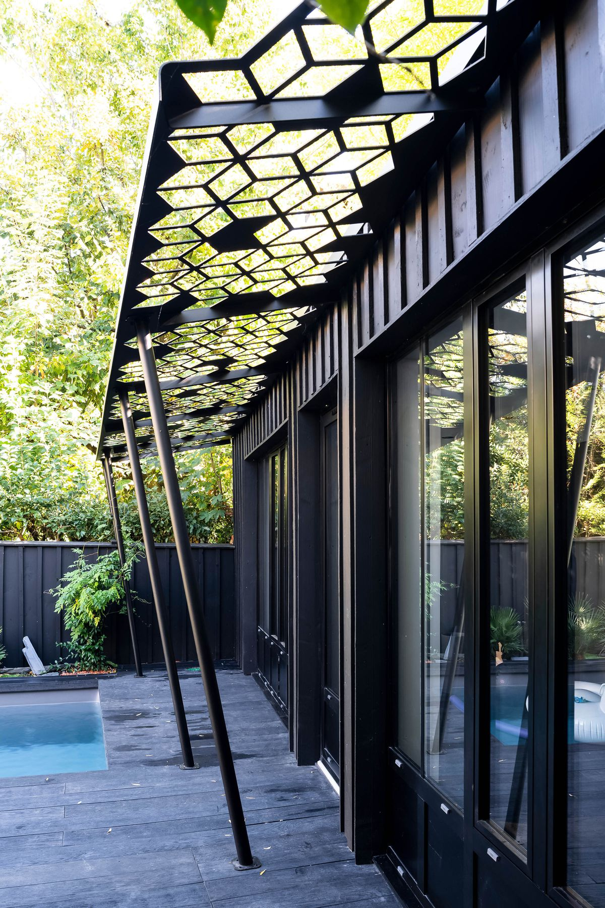 A modern metal pergola with a geometric cut out is attached to the side of a house, next to a pool.