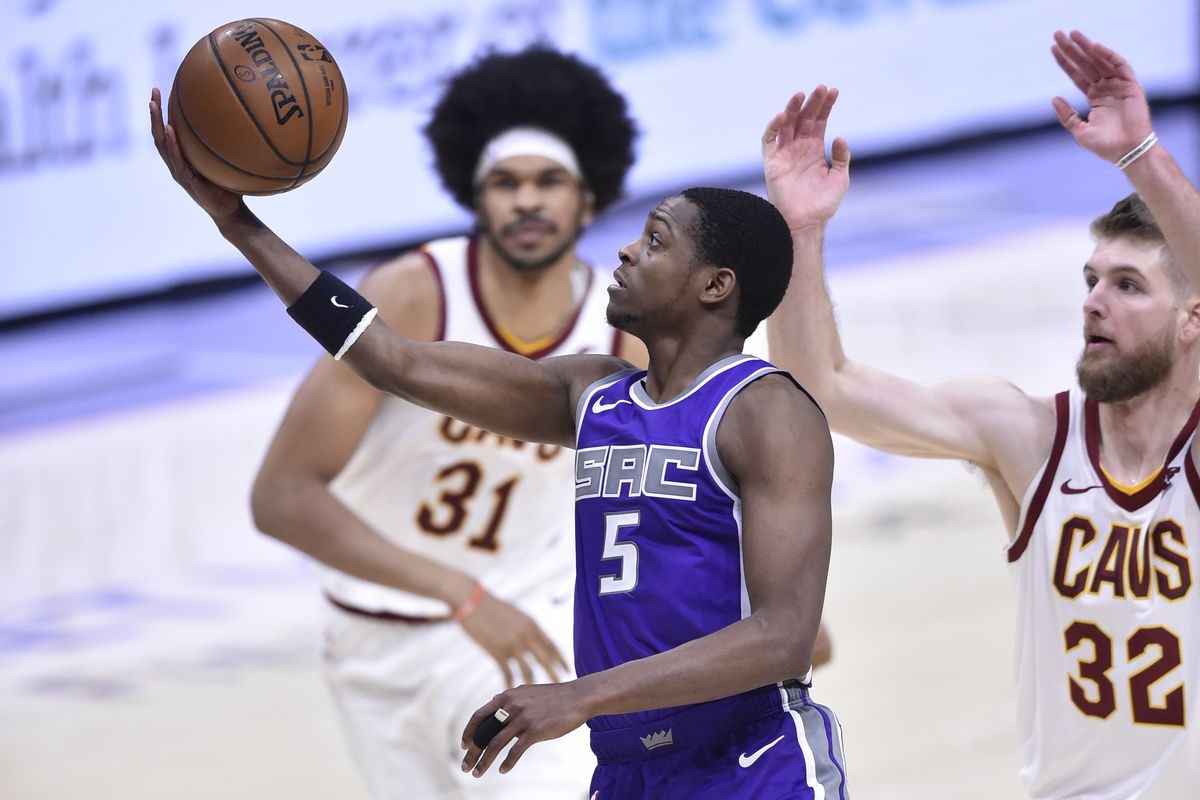 Sacramento Kings guard De'Aaron Fox (5) drives past Cleveland Cavaliers center Jarrett Allen (31) and forward Dean Wade (32) in the fourth quarter at Rocket Mortgage FieldHouse.