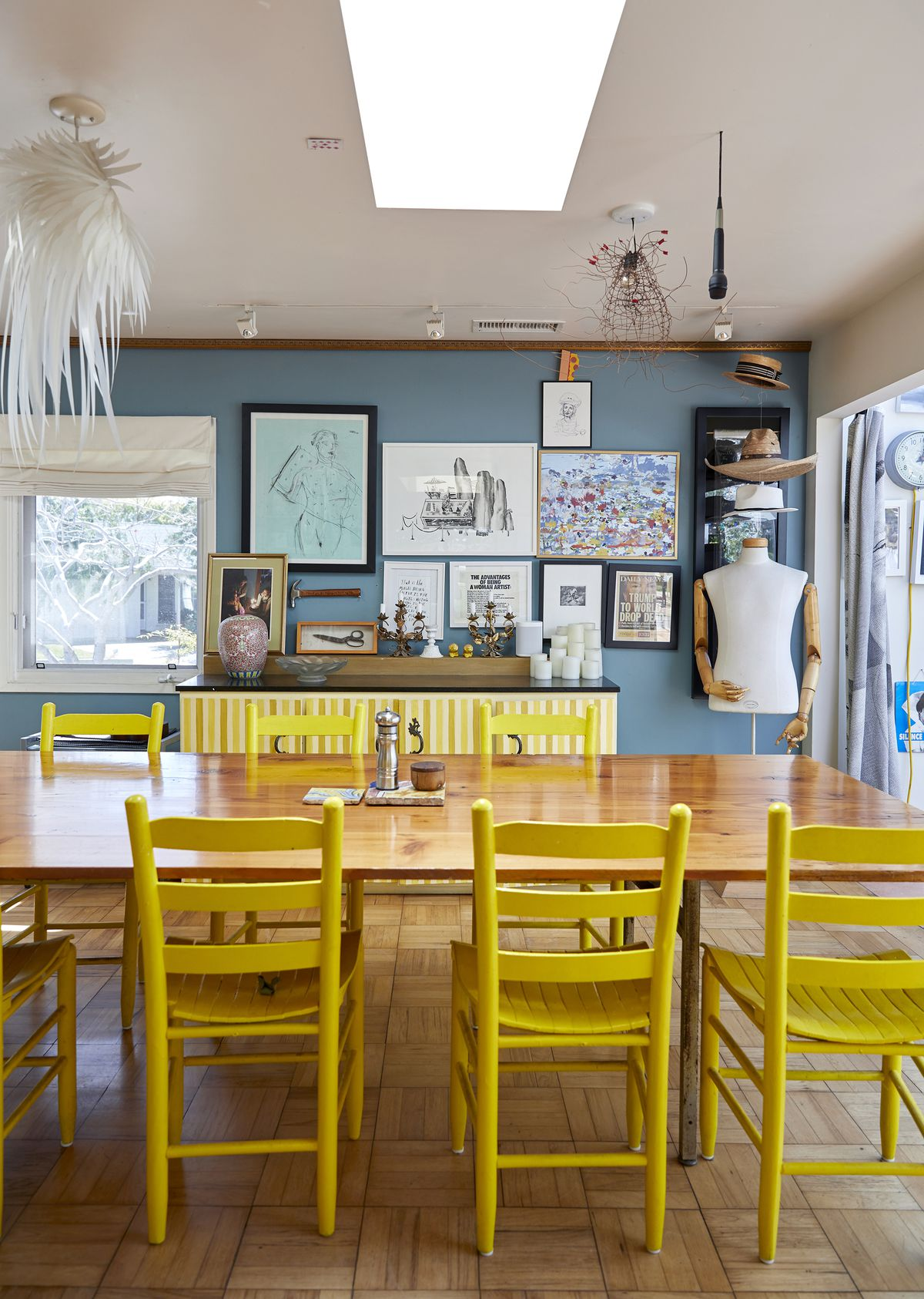 In the foreground is a wooden table with multiple yellow painted chairs. In the distance is a blue painted wall with many framed works of art. Light fixtures and art hang from the ceiling.