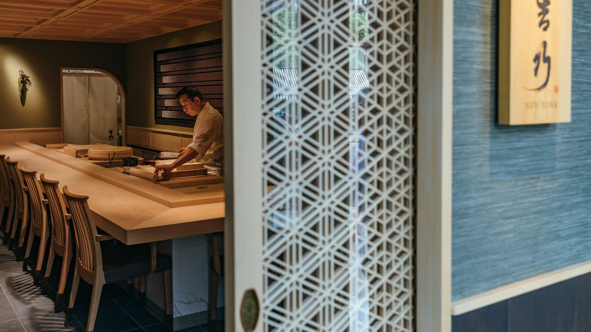 A front view into a sushi restaurant with a view of a sign and a long wooden sushi counter with one chef preparing fish