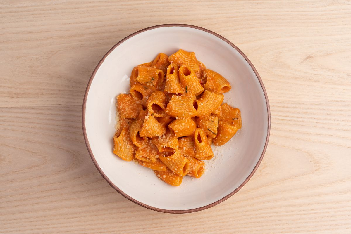 Orange-sauced spicy rigatoni in a bowl, shown from above.