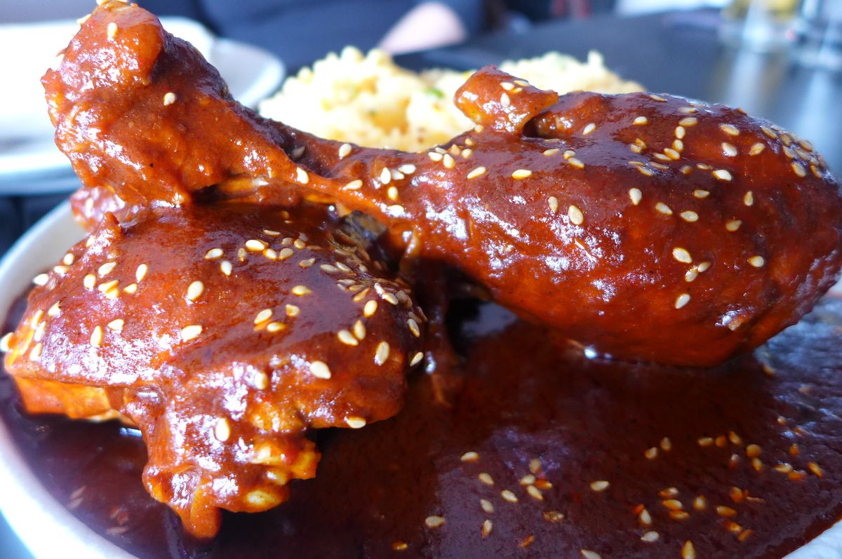 Two pieces of chicken in a dark red sauce sprinkled with sesame seeds.