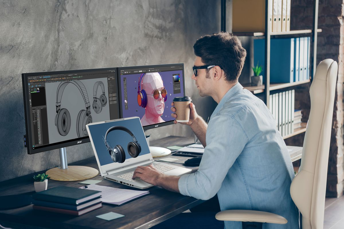 A user views a 3D model of black headphones on a white ConceptD notebook with a blue background. To its left is a pile of three notebooks, a notepad, and a small potted plant. The user holds a coffee in their right hand. Behind the notebook are two external monitors where the user edits a 2D version of the image in editing software. To the right of the desk is a bookshelf.