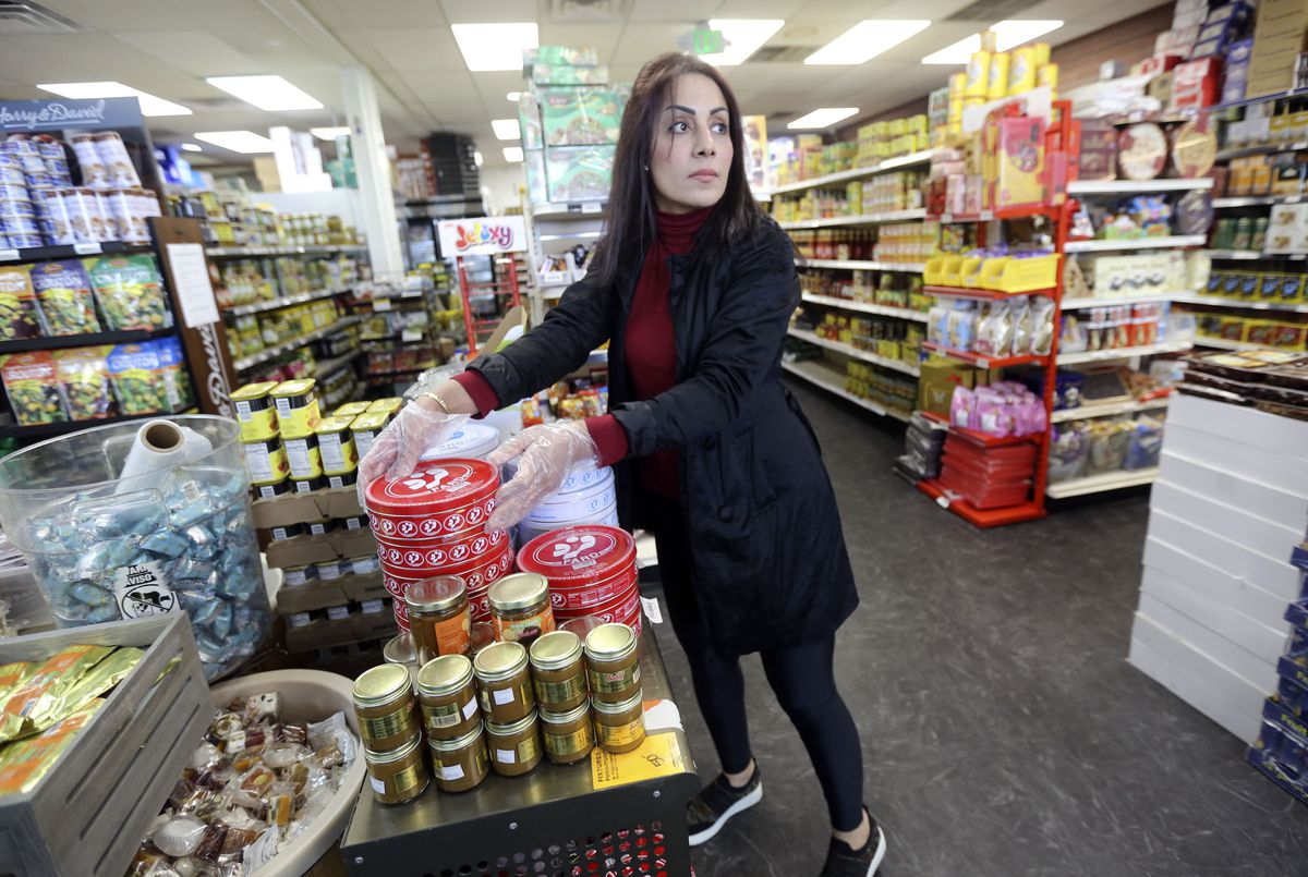 Leila Sabat, manager at Specialty Market in Midvale, stocks goods at the store on Wednesday, March 25, 2020. Small businesses are struggling with a loss of business during the COVID-19 pandemic.