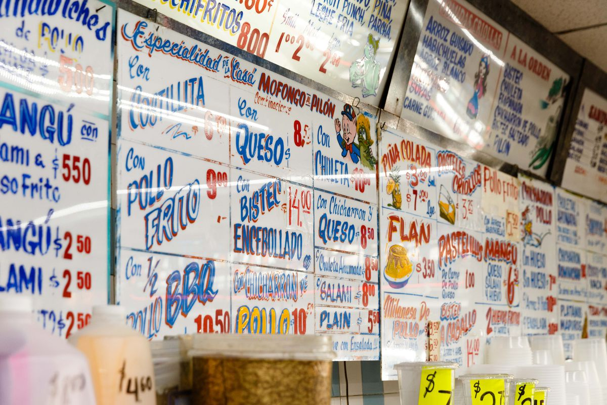Decorative menu signs, in blue and red handwriting, hang for customers to view