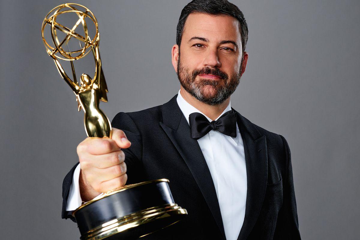 Jimmy Kimmel holding an Emmy Award statue.
