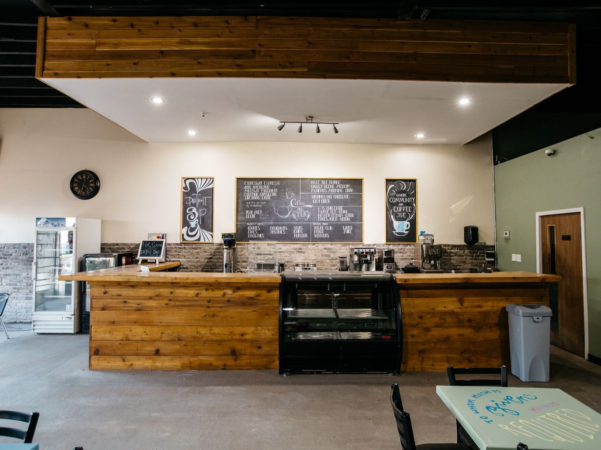 The coffee counter at Detroit sip is paneled with wood and flanked by a light green wall.