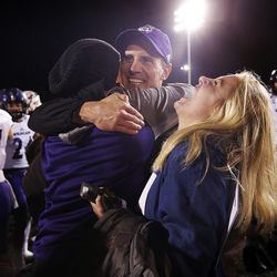 Weber State Wildcats head coach Jay Hill hugs his wife Sara as his daughter Ashtyn cheers after the Wildcats defeat the Southern Utah Thunderbirds in NCAA football in Cedar City on Saturday, Dec. 2, 2017.