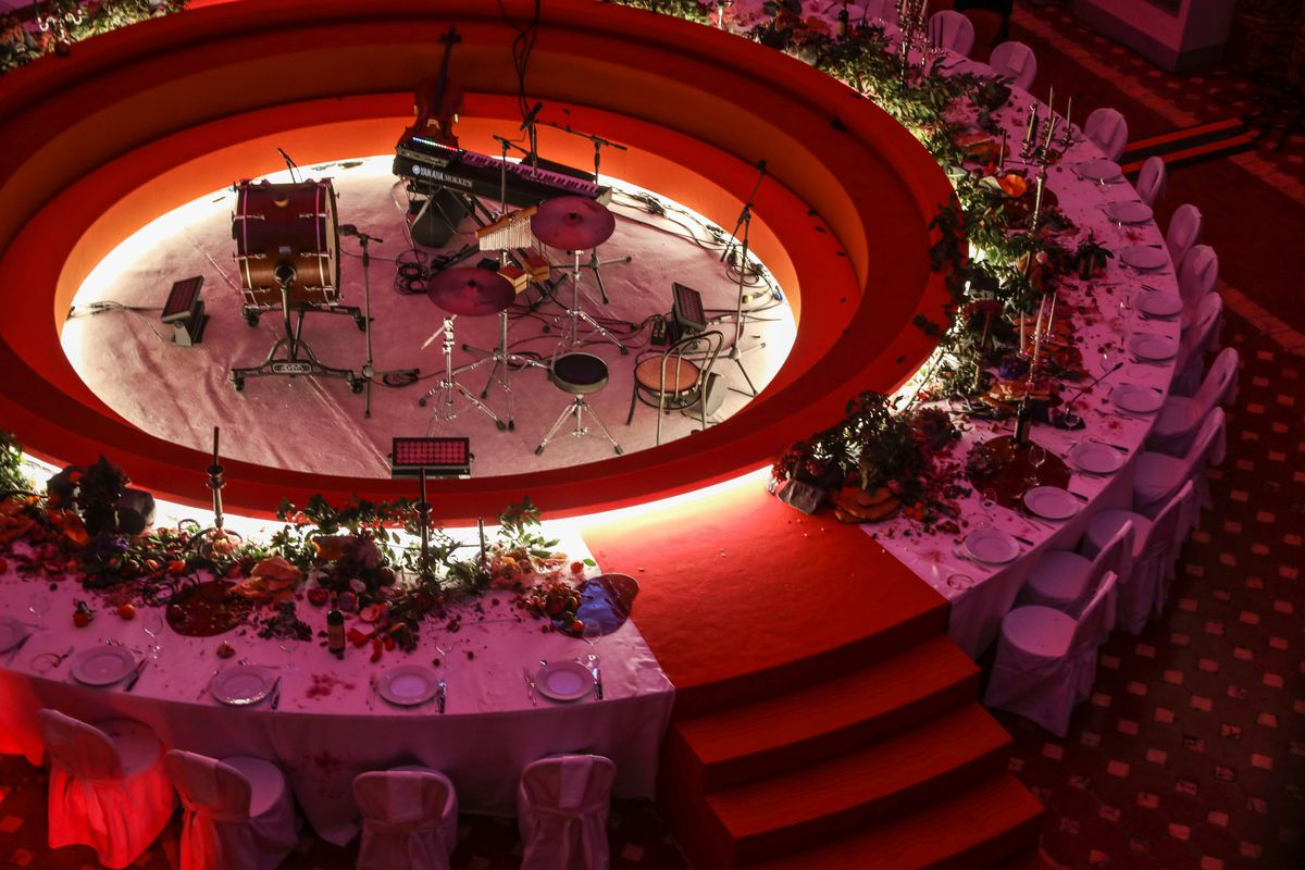 A large round table set up for dinner with music pit in the center.
