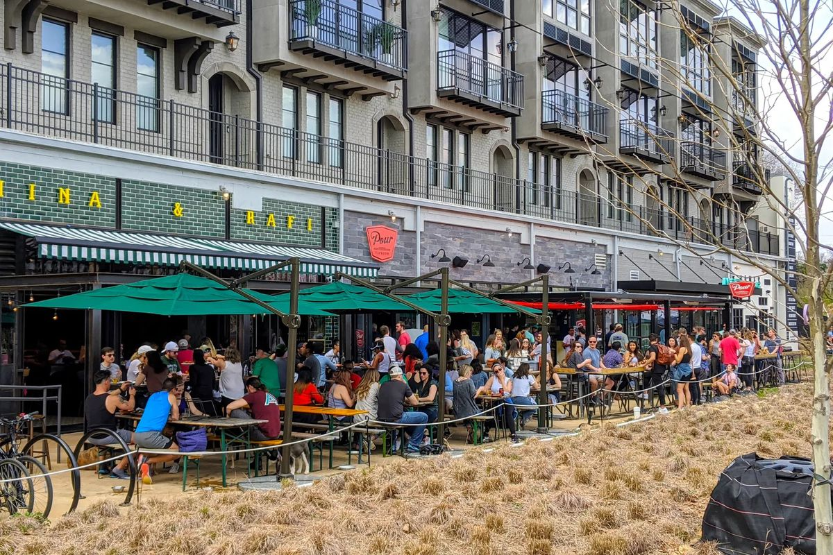 Crowds of people sit at picnic tables outside a restaurant on the Beltline.
