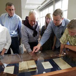 """Visitors look at an 1830 Book of Mormon with an example of Joseph's Smith's handwriting in it at the """"Treasures of the Collection"""" exhibit at the Church History Library."""