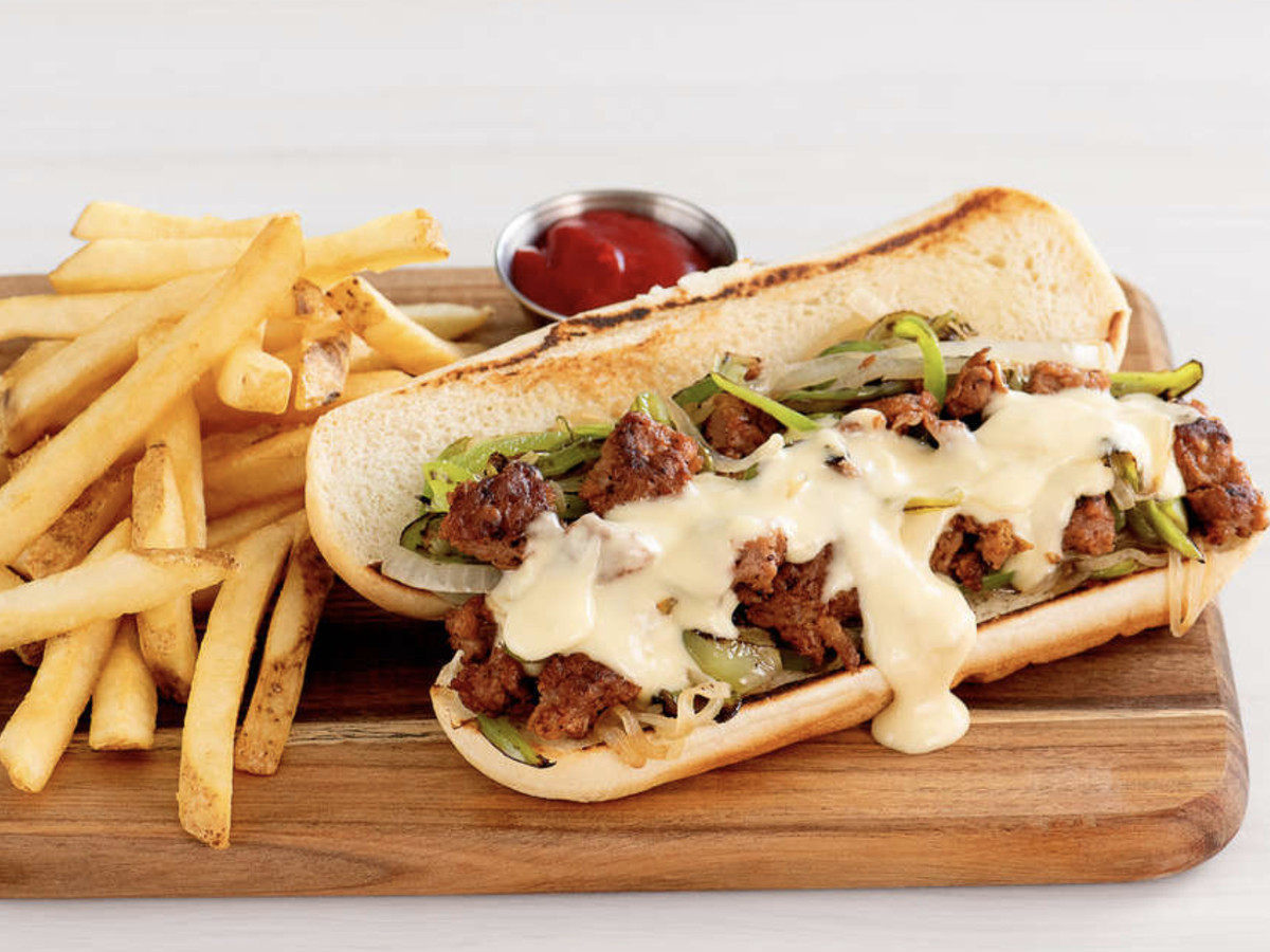 A vegan cheesesteak made of Beyond Burger, topped with peppers, onions, and cheese alternative, and served with french fries