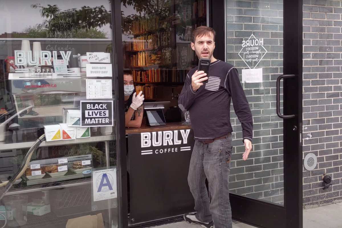 A man holding a cellphone stands in front of a coffee shop and a barista can be seen standing inside