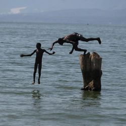 In this Sept. 6, 2012 photo, youths jump into Lake Azuei in Thomazeau, Haiti, near the border with the Dominican Republic. The waters' rise has worsened exponentially in recent years, especially after heavy rains in 2007 and 2008 hit the island of Hispaniola. Tropical Storm Isaac dumped more water on the region last month, sparking more damage.