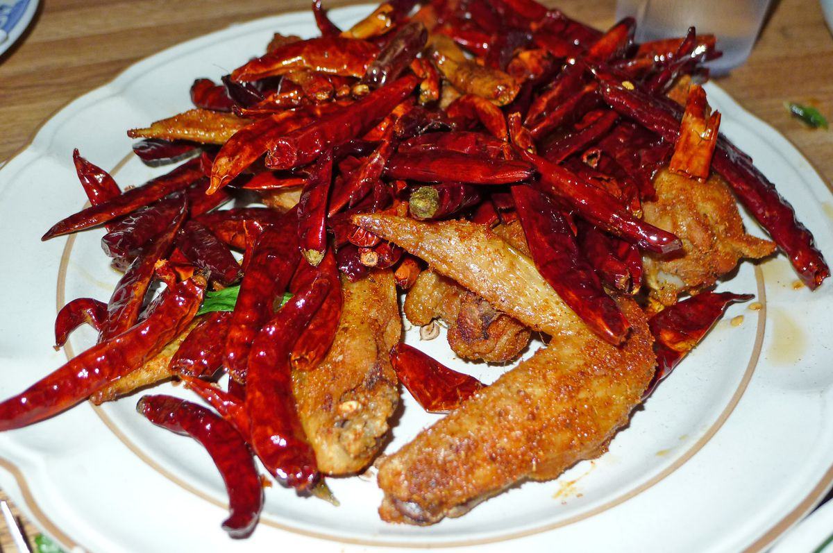 A few fried chicken wings heaped with dried red peppers.