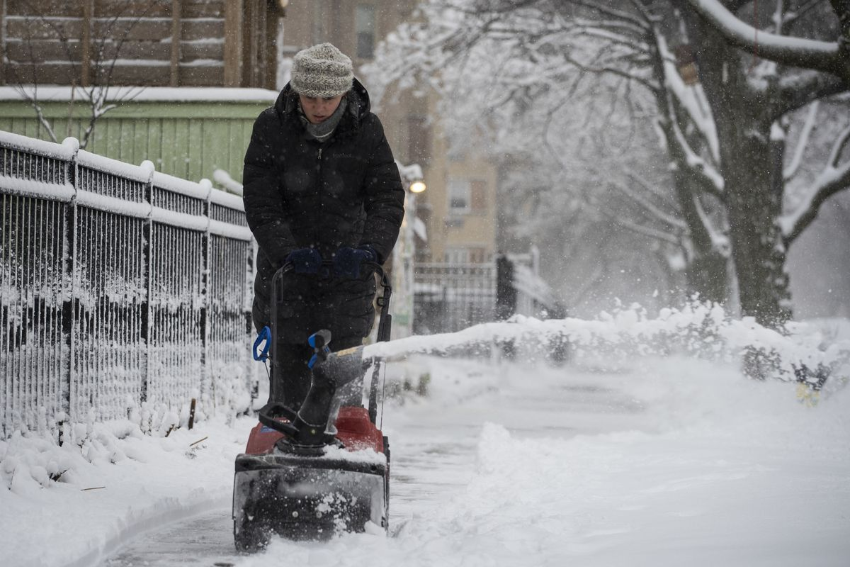 A woman plows the sidewalk near North Ridge Boulevard and West Birchwood Avenue in Rogers Park after more than three inches of snow fell during a winter storm that moved through the Chicago area overnight, Tuesday morning, Jan. 26, 2021.
