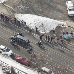 People watch as the funeral procession for Unified police officer Doug Barney makes its way through Holladay, where Barney served, on its to the Orem City Cemetery, where he will be laid to rest on Monday, Jan. 25, 2016. Barney was shot and killed in the line of duty by a man who seemingly had done nothing more than leave the scene of a traffic accident Sunday, Jan. 17, 2016.
