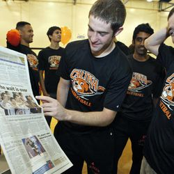 Caltech basketball players Mike Paluchniak, left, Arjun Chandar, middle partially blocked, and Mike Edwards, right, smile as they look at a local sports page announcing their 46-45 win over Occidental College in a Division III NCAA college basketball game in Pasadena, Calif. on Wednesday, Feb. 23, 2011. The Beavers ended their 310-game conference losing streak with a one-point victory in the season finale on Tuesday.