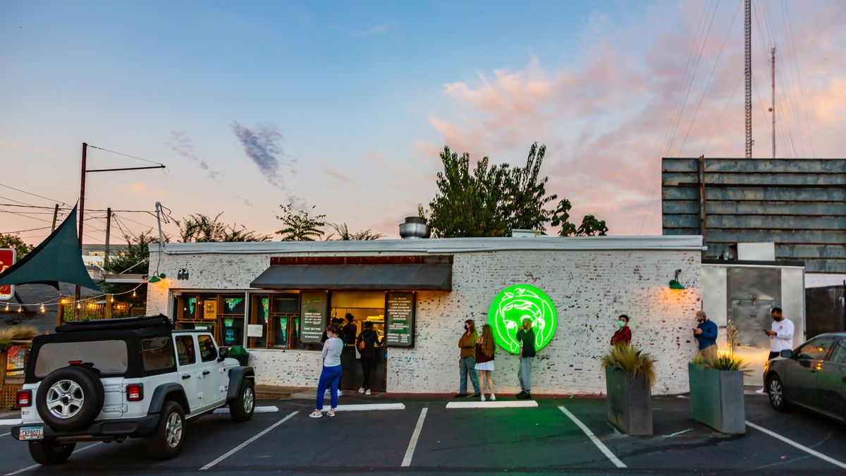 A line of people standing socially distanced and in masks ready to order from Supremo Taco's to-go window. The shot is taken from the parking lot looking toward the white painted brick building with the bright neon green Supremo logo lit up as the evening sun sets, A white Jeep is parked to the left