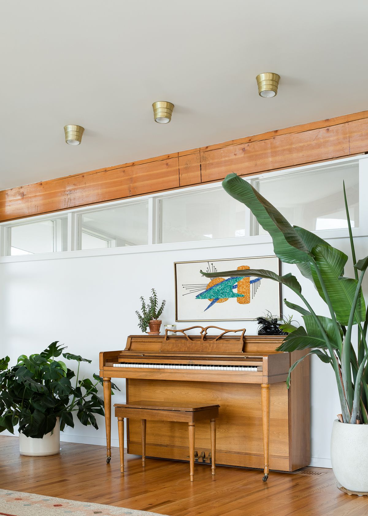A piano sits against a white wall. There is a large framed work of art hanging over the piano, The piano is flanked by multiple houseplants.