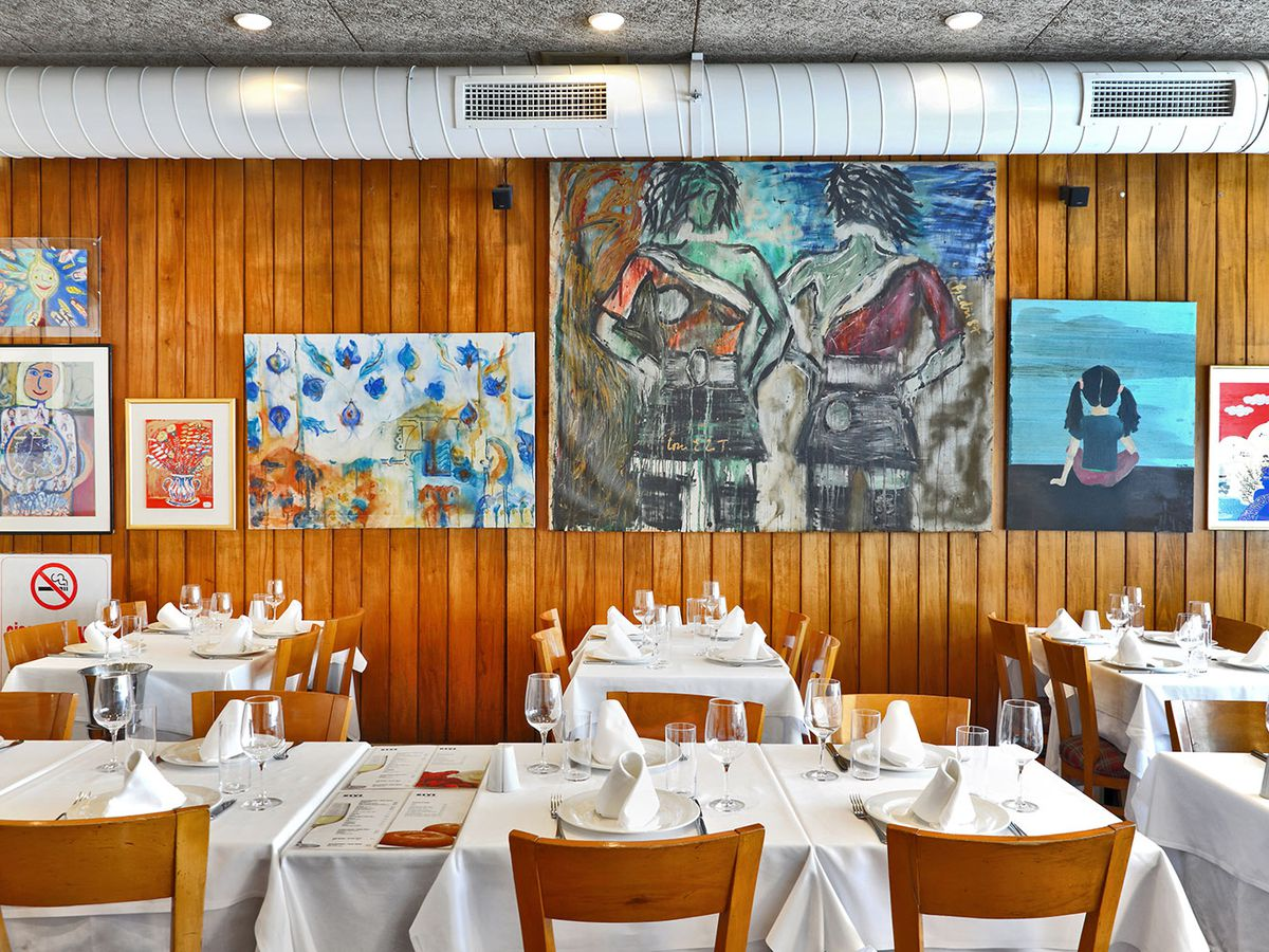 A wood-paneled dining room with bright illustrations on the walls and white tablecloths and place settings on the tables
