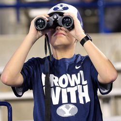 A young BYU fan uses a pair of binoculars to view the players as they warm up as BYU and Mississippi State play in Provo at LaVell Edwards Stadium on Friday, Oct. 14, 2016.