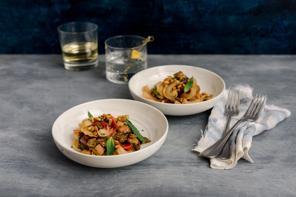 Two white bowls of pasta with bacon, eggplant, and pinenuts sit on a gray table with cocktails in the background