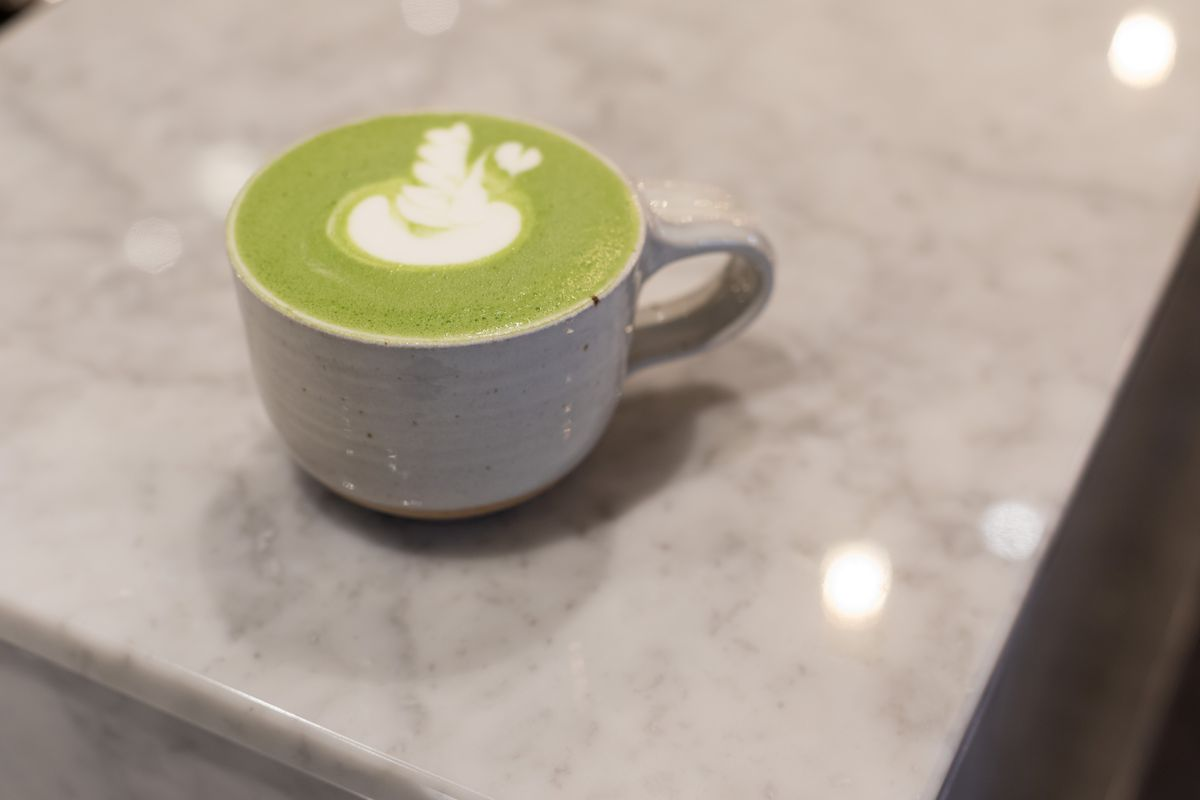 A bright green matcha latte on a marble counter