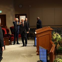 President Russell M. Nelson and President Dallin H. Oaks of The Church of Jesus Christ of Latter-day Saints' First Presidency wave to other leaders and speakers as they walk into a small auditorium at the Church Office Building on Saturday, April 4, 2020. The talks are being broadcast all over the world for this weekend's digital-only 190th Annual General Conference.