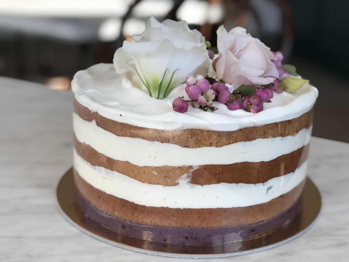 A three tiered cake with bare sides topped with whipped cream