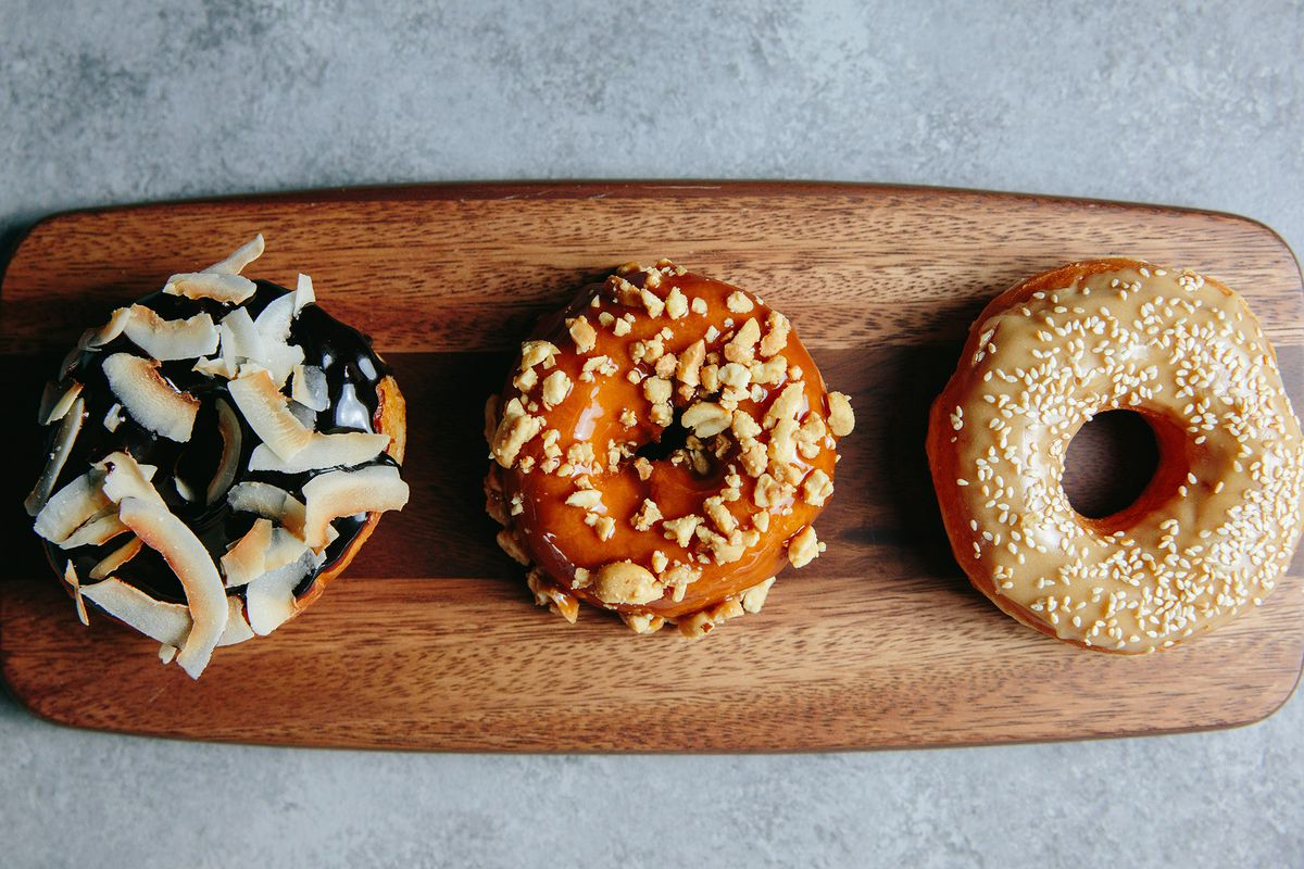 Three doughnuts with different glazes and toppings sit in a row on a narrow wooden plank at Chickadee in Boston's Seaport District.