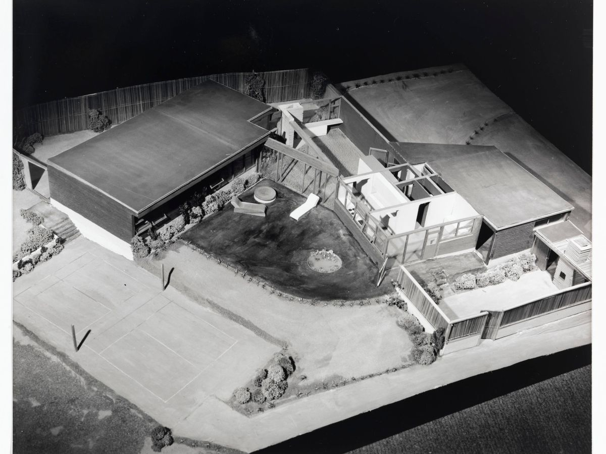 The aerial view of a group of buildings. All the buildings have flat roofs. There is a yard in the center of the group of buildings.