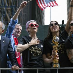 From left, U.S. Soccer Federation President Carlos Cordeiro, New York Mayor Bill de Blasio and U.S. women's soccer players Megan Rapinoe and Alex Morgan join teammates and others as the U.S. women's soccer team is celebrated with a parade.