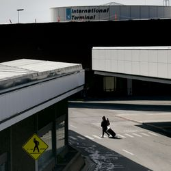"""A lone traveler walks to the parking lot of the Salt Lake City International Airport on Wednesday, April 8, 2020. Utah Gov. Gary Herbert announced new efforts on Wednesday """"to protect the people of Utah and slow the spread of coronavirus in the state"""" by closely monitoring its borders, as well as passengers who fly into the airport."""