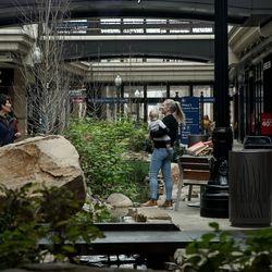 Shoppers walk across a water feature in City Creek Center in Salt Lake City on Friday, March 13, 2020.
