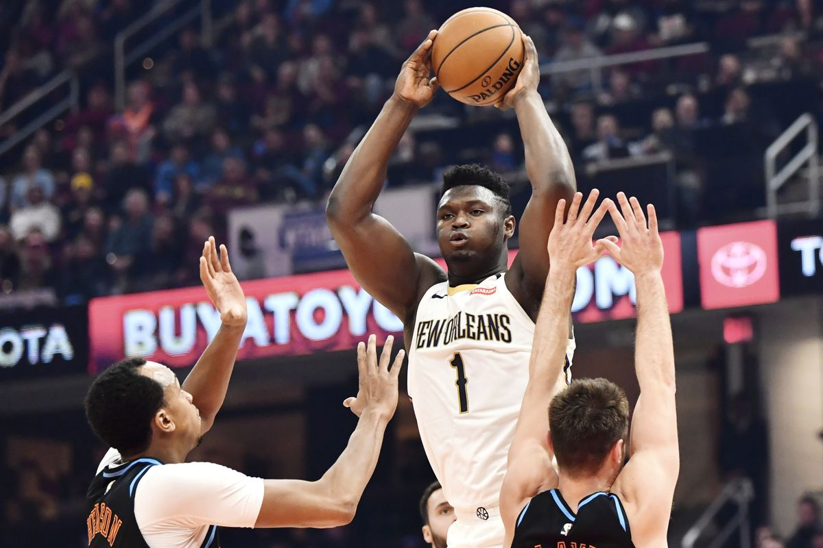 New Orleans Pelicans forward Zion Williamson looks to pass over Cleveland Cavaliers forward John Henson and guard Matthew Dellavedova  during the first half at Rocket Mortgage FieldHouse.