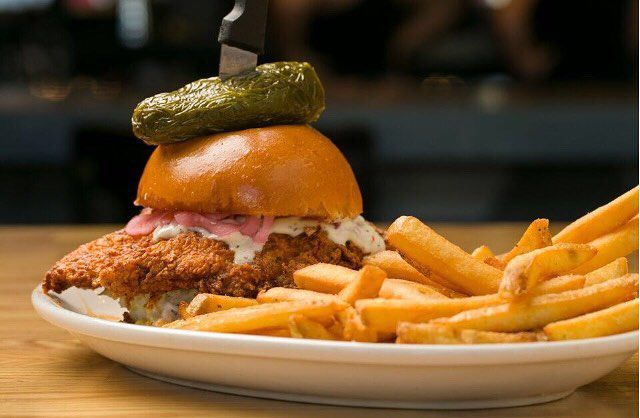 Nashville hot chicken sandwich on a plate with french fries