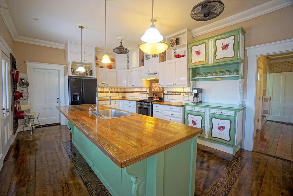 A kitchen with a large center island, wood floors, white and green cabinets.