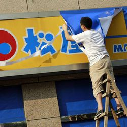 FILE - In this Monday, Sept. 17, 2012 file photo, A worker covers a signboard of a Japanese restaurant chain with blue sheets ahead of major protests expected on Tuesday, Sept. 18 near the Japanese Consulate General in Shanghai, China. Scores of Japanese-owned factories and stores in China were shuttered Tuesday as anti-Japanese demonstrations raged in dozens of cities. At stake are billions of dollars in investments and far more in sales and trade between Japan and China, the world's third- and second-largest economies. The two are so closely entwined, though, that both would suffer from any long-term disruptions.