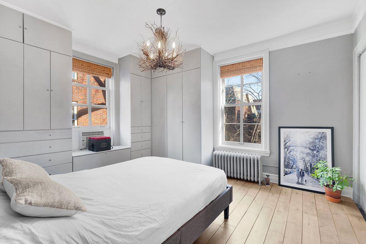 A bedroom with a small bed, hardwood floors, grey walls, two windows, and a chandelier.